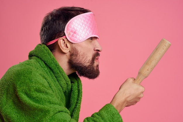 Portrait of a man in a pink sleep mask and a wooden rolling pin emotions green robe irritability model. high quality photo