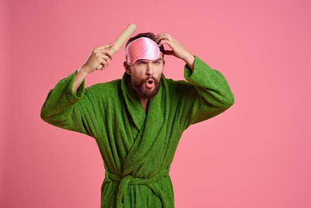 Portrait of a man in a pink sleep mask and a wooden rolling pin emotions green robe irritability model