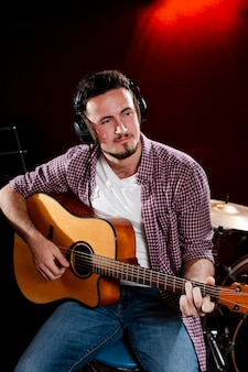 Portrait of a man playing guitar and wearing headphones
