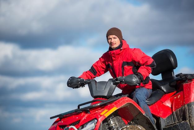 Portrait of man on red quad bike
