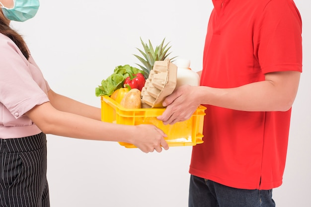 Portrait of a man in red uniform is holding fresh food in plastic box on white background,  home delivery concept