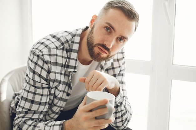 Portrait of man relaxing at home with cup of coffee