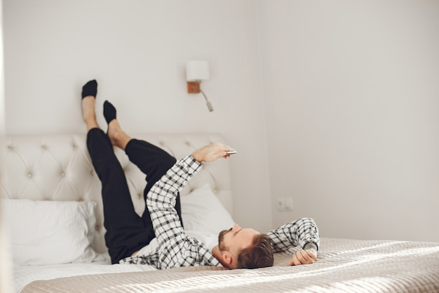 Ritratto di uomo in un momento di relax a casa con lo smartphone