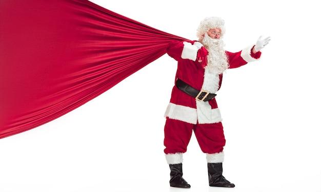 Ritratto di uomo in costume da babbo natale - con una lussuosa barba bianca, cappello di babbo natale e un costume rosso - a figura intera isolato su uno sfondo bianco con un grande sacco di regali