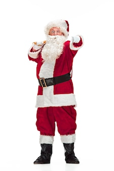 Portrait of man in santa claus costume - with a luxurious white beard, santa's hat and a red costume - in full length isolated on a white background