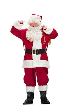 Ritratto di uomo in costume di babbo natale con una lussuosa barba bianca, cappello di babbo natale e un costume rosso - in piena lunghezza isolato su bianco