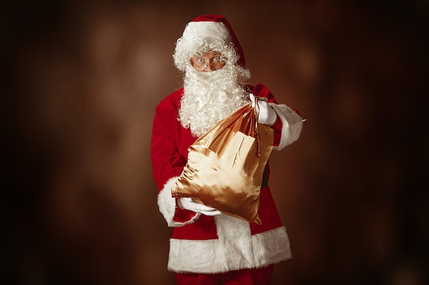Portrait of man in santa claus costume - with a luxurious white beard, santa's hat and a red costume at red studio background with gifts