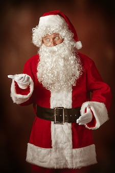 Portrait of man in santa claus costume - with a luxurious white beard, santa's hat and a red costume at red studio background