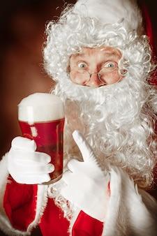Ritratto di uomo in costume di babbo natale con una lussuosa barba bianca, cappello di babbo natale e un costume rosso in rosso con birra