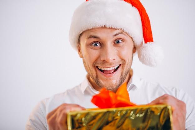 Portrait of man in santa hat holding christmas golden present box