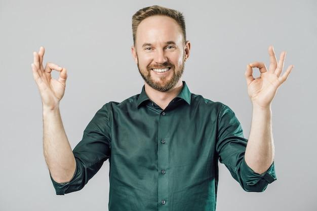Portrait of man showing okay gesture