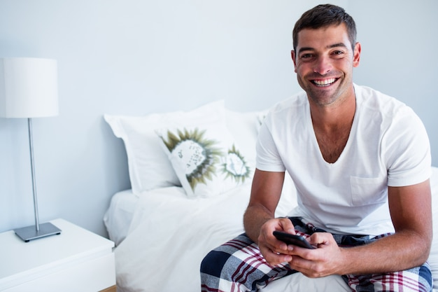 Portrait of man sitting on bed and typing a text message on phone