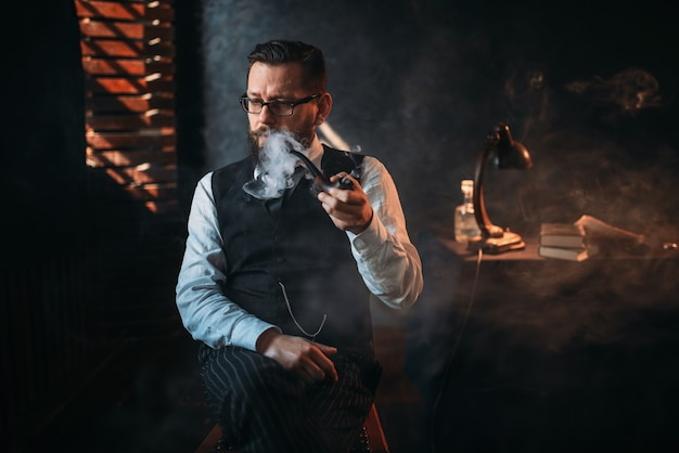 Portrait of man sitting on chair and smoking pipe