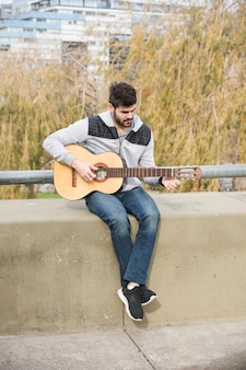 Portrait of a man sitting on retaining wall playing guitar
