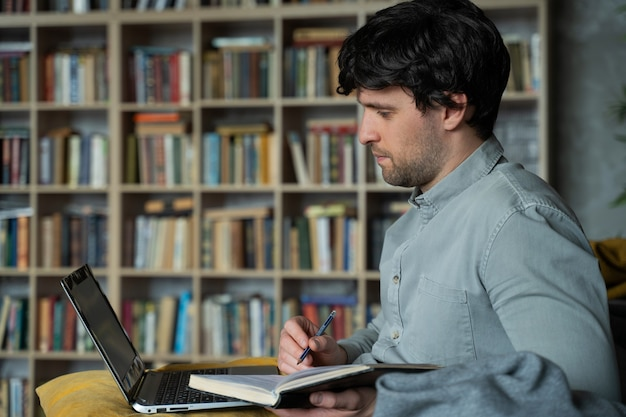 Portrait of a man sitting on a sofa with a laptop against bookshelf