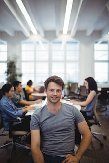 Portrait of man smiling at camera while colleagues working in ba