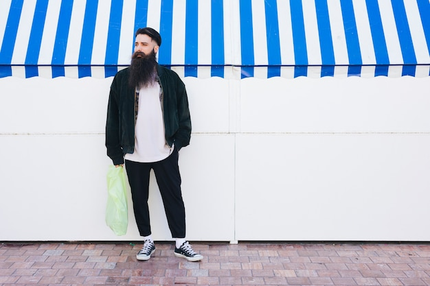Portrait of a man standing in front of awning holding plastic carry bag