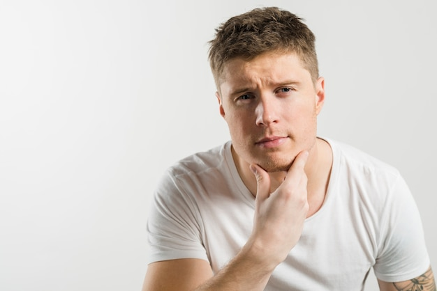 Portrait of a man strokes his chin after shaving against white backdrop
