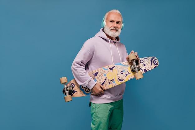 Portrait of man in stylish hoodie holding skate board