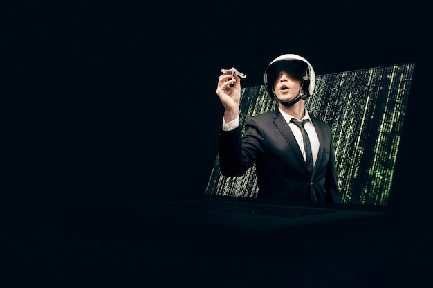 Portrait of a man in a suit and helmet. he launches a paper airplane from a laptop screen.