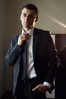 Portrait of a man in a suit and tie near the window. the groom is preparing for the wedding ceremony