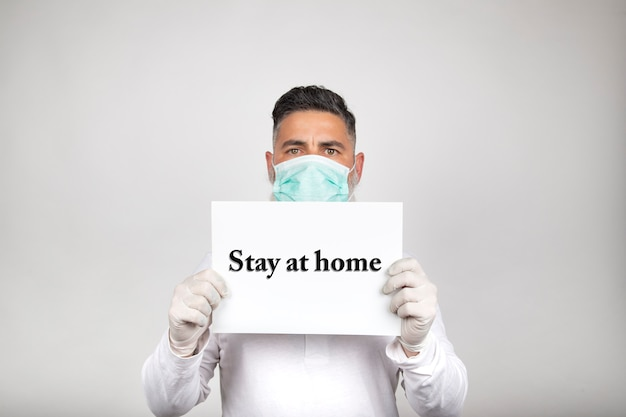 Portrait of man in surgical mask holding a white sign with the phrase stay home on white background. coronavirus prevention