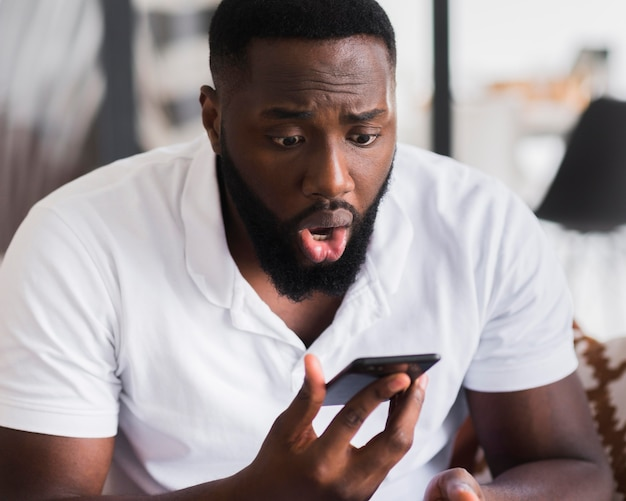Portrait of man surprised after watching his phone