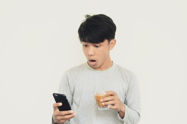 Portrait of a man surprised to see a cell phone while carrying coffee