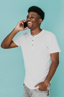 Portrait of man in t-shirt smiling while talking on smartphone