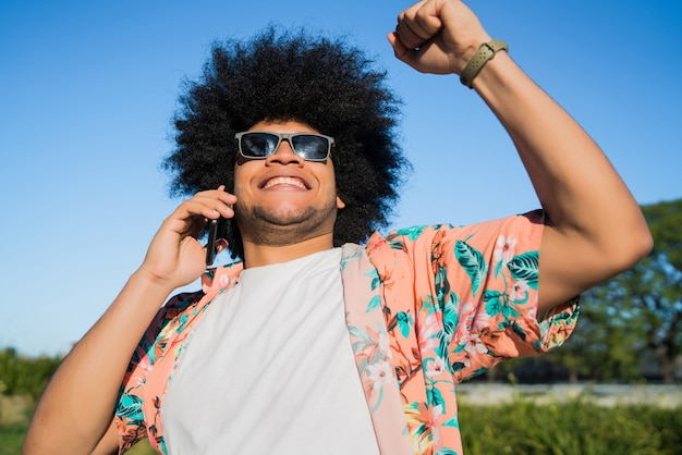 Portrait of man talking on the phone and celebrating good news outdoors on the street