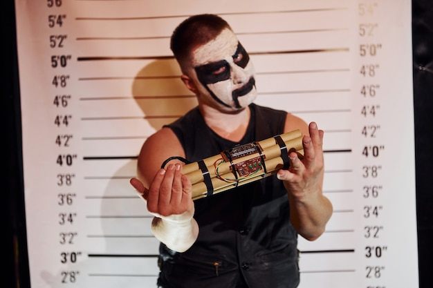 Portrait of man that is on the thematic halloween party in scary black metal makeup and costume with bomb in hands.