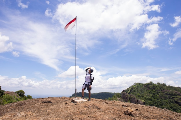 Portrait of man on top of the hill rising indonesian flag celebrating independence day