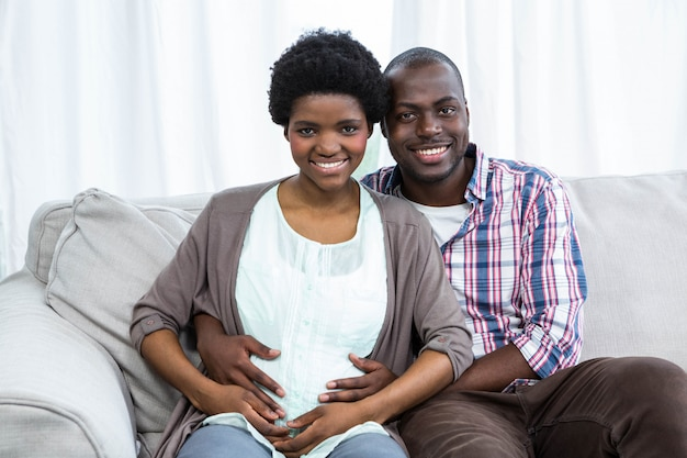 Portrait of man touching pregnant womans stomach on sofa at home