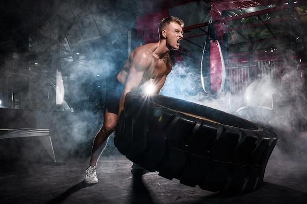 Portrait man training with tire
