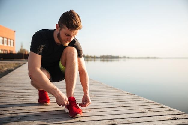 Ritratto di un uomo che lega i lacci delle scarpe sulla scarpa sportiva