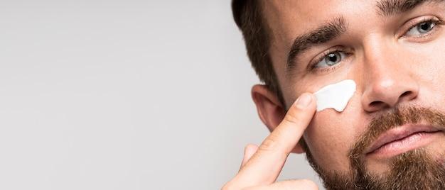 Ritratto di uomo che utilizza crema per il viso con copia spazio