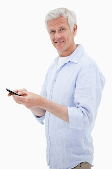 Portrait of a man using his mobile phone while looking at the camera
