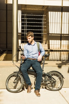 Portrait of a man using mobile phone sitting with bicycle