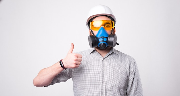 Portrait of man using respirator and wearing helmet and showing thumb up gesture