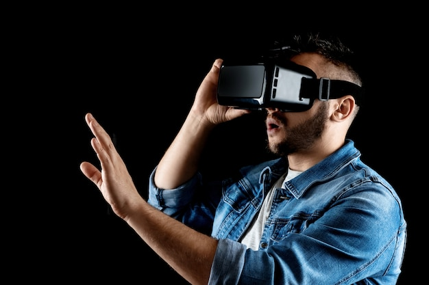 Portrait of a man in virtual reality glasses, vr, against a dark background.