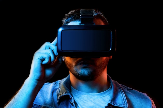 Portrait of a man in virtual reality glasses, vr, against a dark background