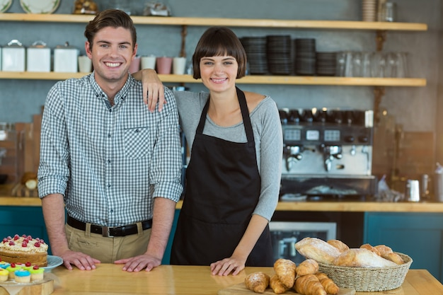 Portrait of man and waitress standing at bread counter