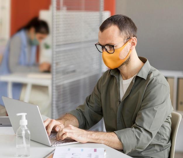 Ritratto di uomo che indossa la maschera per il viso al lavoro