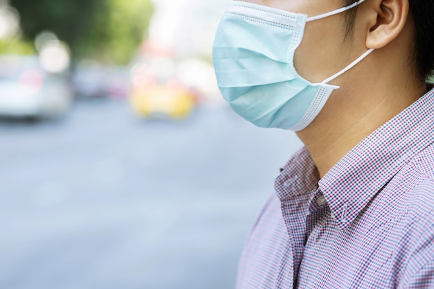 Portrait of man wearing facial hygienic mask nose outdoors.