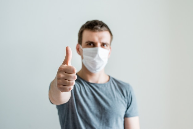 Portrait of man wearing white medical mask and and thumb up, illness on light background. environmental awareness, coronavirus and flu protection concept.