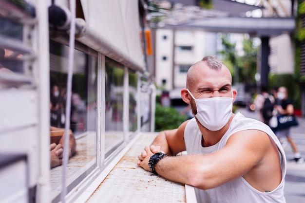 Ritratto di uomo in maschera medica bianca sulla piazza centrale della città si siede su una sedia in van cafe