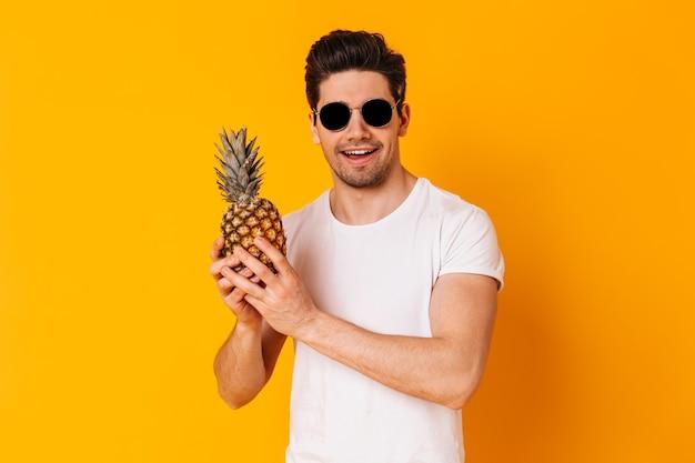Ritratto dell'uomo in maglietta bianca e occhiali da sole che tengono ananas sullo spazio arancione.