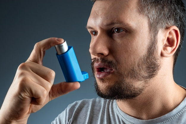 Portrait of a man with an asthma inhaler in his hands, an asthmatic attack. the concept of treatment of bronchial asthma, cough, allergies, dyspnea.