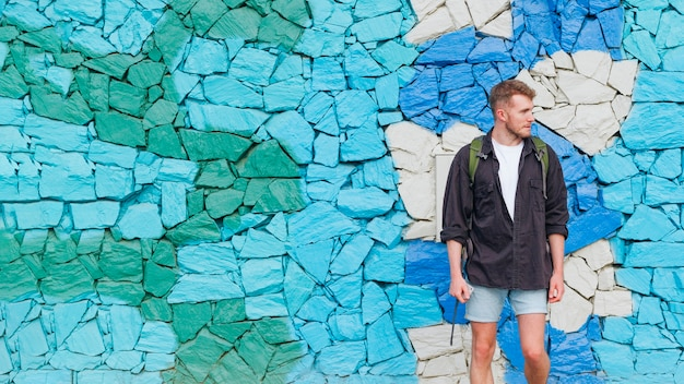 Portrait of man with backpack standing against painted stone wall