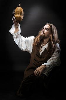 Portrait of a man with a beard and long hair wearing a medieval pirate costume on a black wall, a pirate holding a ripe pumpkin